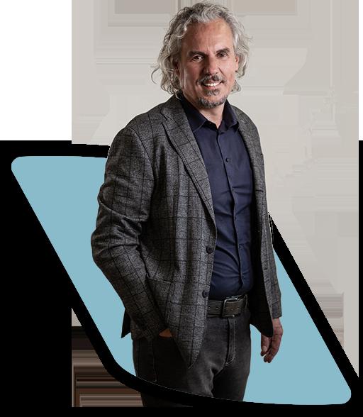 Ein Foto, das den Gründer, Gesellschafter und Geschäftsführer Frank Nowicki in einem dunkelgrau karierten Jackett mit dunkelblauem Hemd zeigt. Mit einer Hand in der Hosentasche lächelt er freundlich in die Kamera.