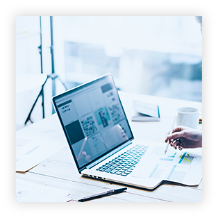 Ein Foto von einem Arbeitsplatz, auf dem ein aufgeschlagener Laptop zu sehen ist. Eine Kaffeetasse, Unterlagen, ein kleines Taschenbuch sowie zwei Stifte sind ebenfalls zu erkennen. Das Foto hat einen hellblauen Farbton.