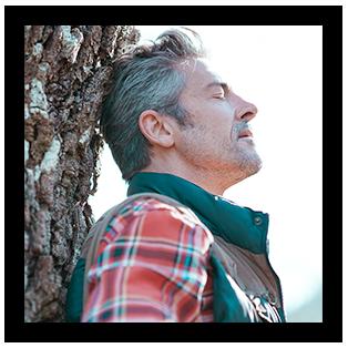 Ein Bildausschnitt eines Mannes mittleren Alters, der an einen Baum gelehnt eine entspannt wirkende Haltung einnimmt. De Augen sind geschlossen, der Kopf dem Licht entgegengestreckt und der Gesichtsausdruck wirkt ruhig.