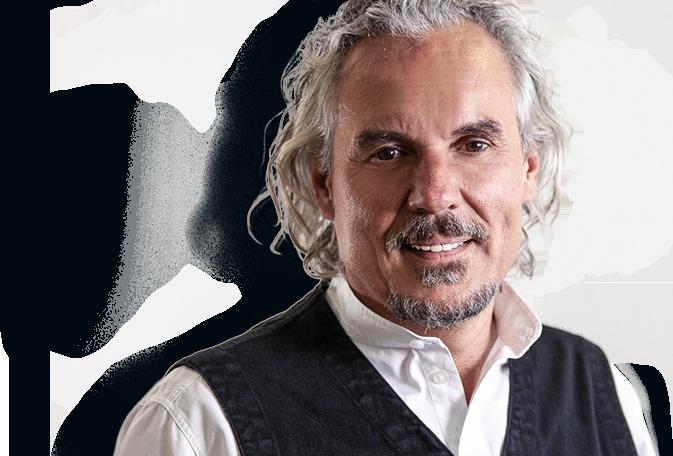 Ein Foto von dem Gründer, Gesellschafter und Geschäftsführer Frank Nowicki, welcher ein weißes Hemd trägt und freundlich in die Kamera lächelt. Der Hintergrund ist türkisfarben.