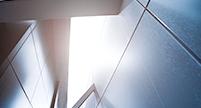 Ein Bildausschnitt eines abstrakten Raumes, wobei ein unterschiedlich starker Lichteinfall zu sehen ist.