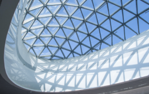 Ein Foto einer Glaskuppel mit einer interessanten Netzkonstruktion, die viele kleinere, dreieckige Fenster verbindet.