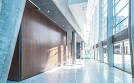 Ein Foto von einem lichtdurchfluteten Eingangsbereich eines Gebäudes. Eine hohe Fensterfont ermöglicht eine strahlende Atmosphäre.
