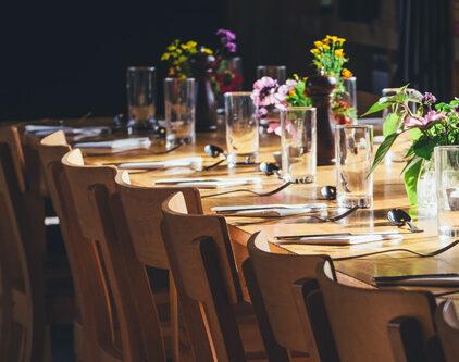 Ein Bildausschnitt eines gedeckten, hellbraun farbenen Tisches mit mehreren Stühlen. Der Tisch ist zudem mit bunten Blumen geschmückt und wird mit Licht angestrahlt.