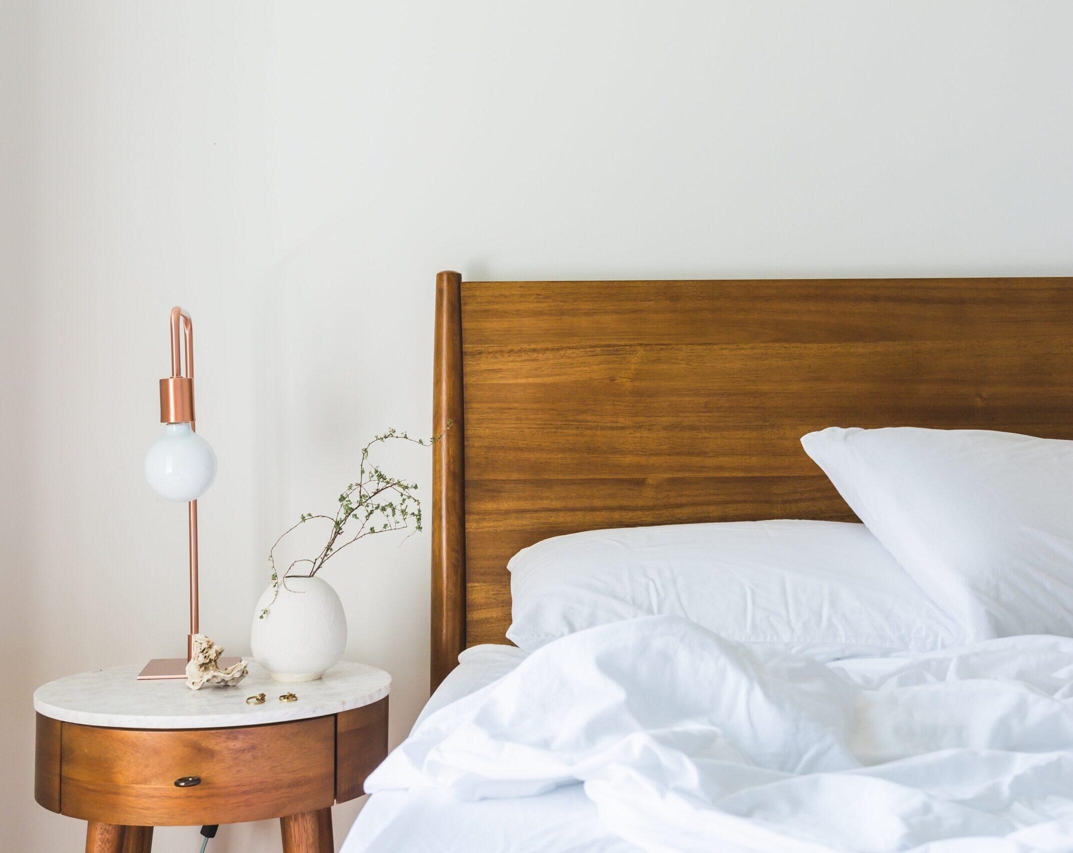 Ein Foto von einem Holzbett und einem Nachtisch mit einer Lampe und einem Blumentopf darauf.
