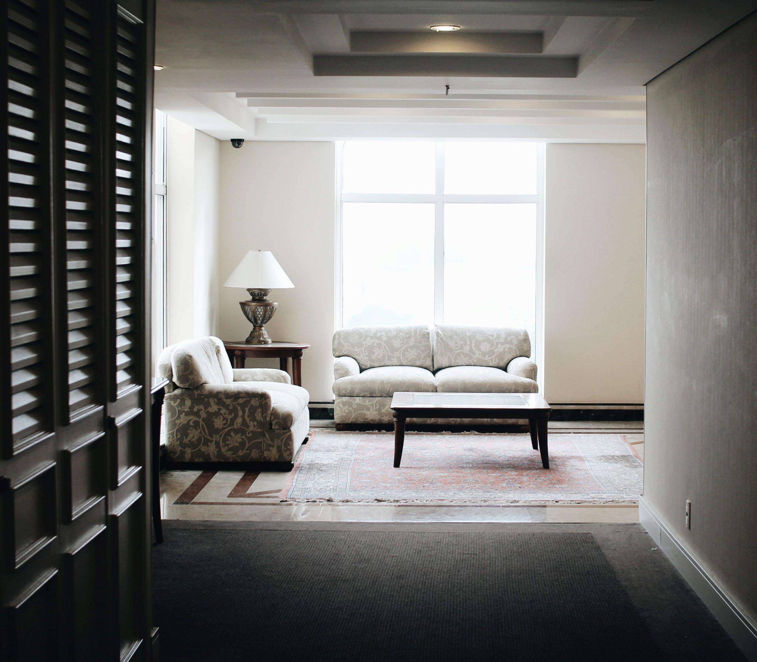 Ein Foto mit Blick auf einen Raum, in welchem sich eine vom Tageslicht beleuchtete Couchecke befindet. Diese wird ergänzt durch eine Lampe und einen kleinen Tisch.