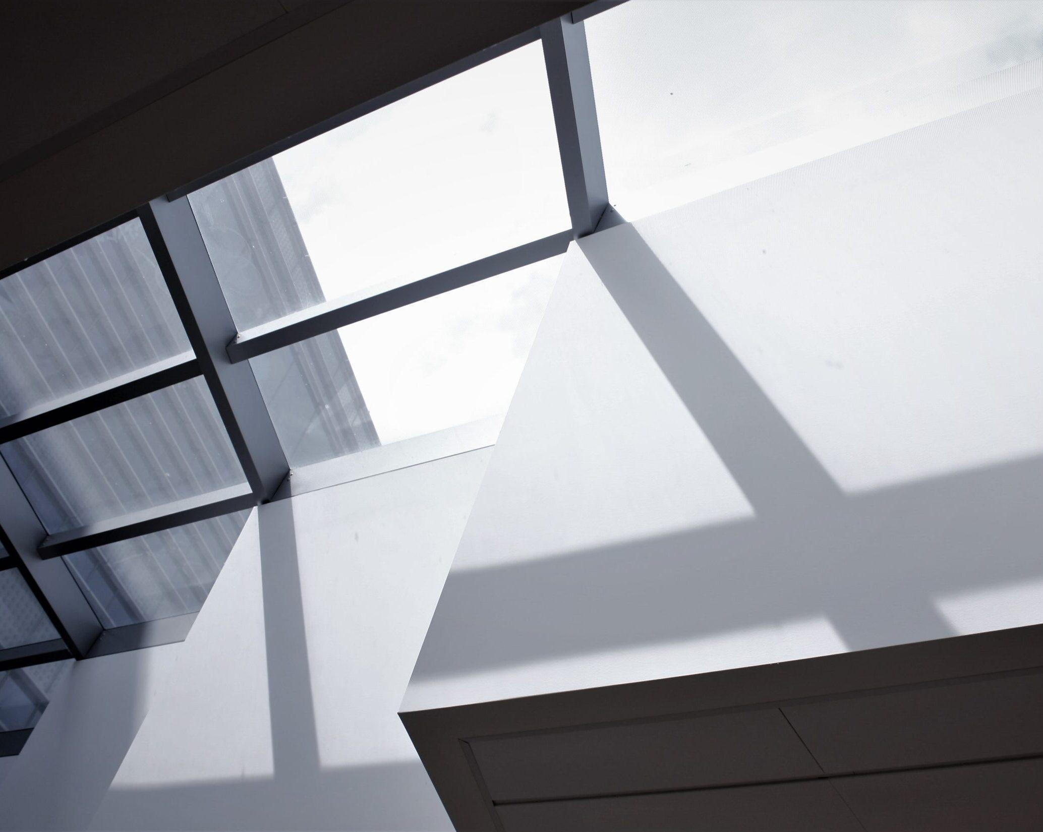 Ein Foto von viereckigen Fenstern, durch die Tageslicht scheint. Die dünnen Balken, welche die einzelnen Fensterscheiben voneinander trennen, werfen Schattenbalken auf die weißen, versetzt angeordneten Wände.