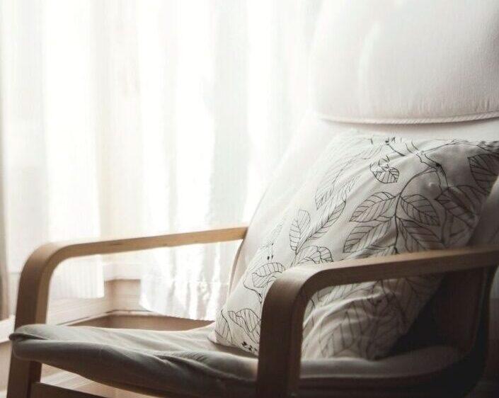 Ein Foto von einem hell gepolsterten Sesselstuhl, auf dem ein helles Kissen mit Blumenmuster liegt.